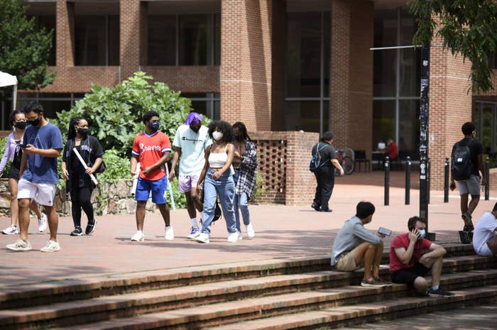 Several students, all wearing masks, walk through the campus of UNC