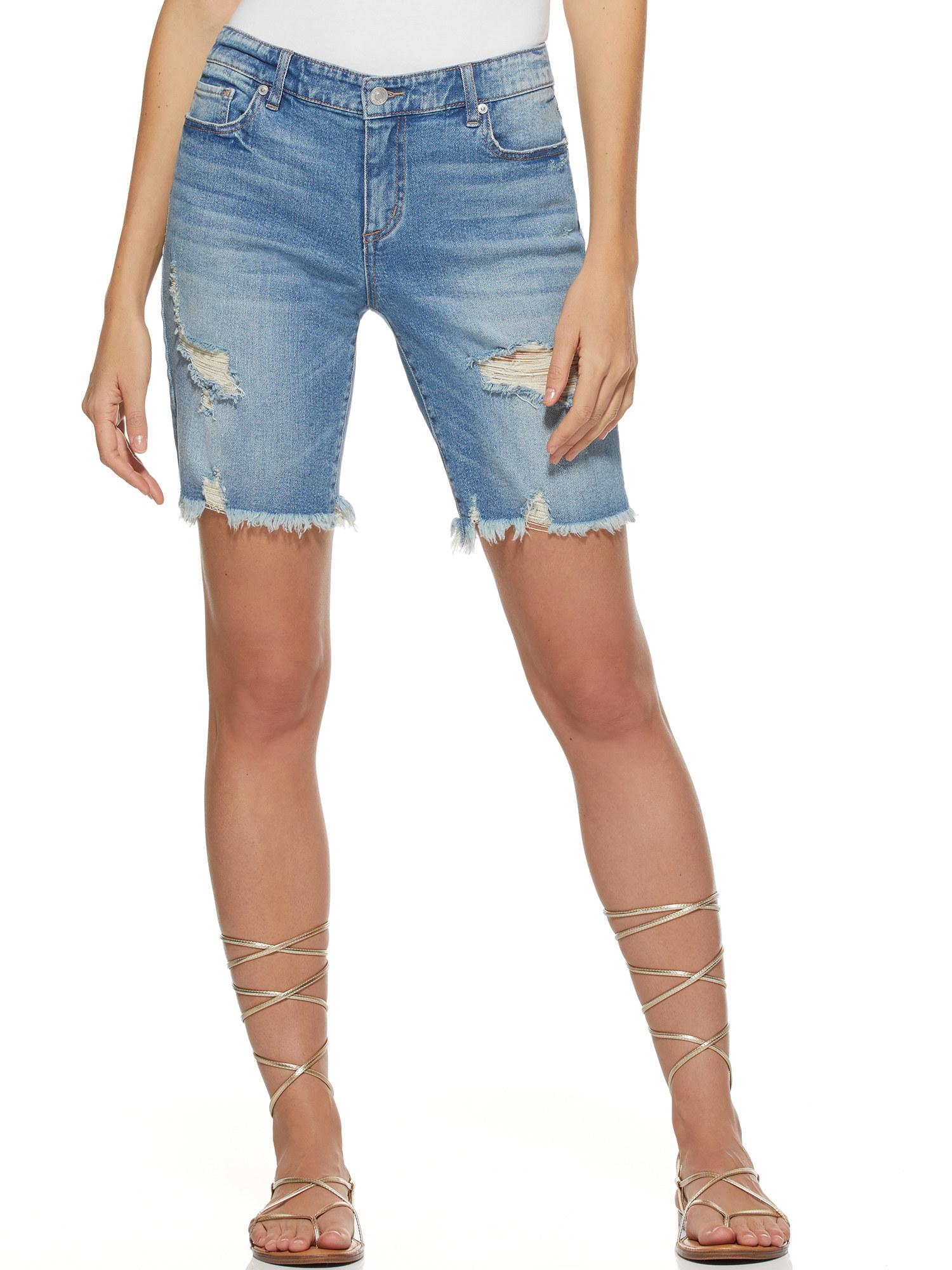 Model in distressed medium denim bermuda shorts