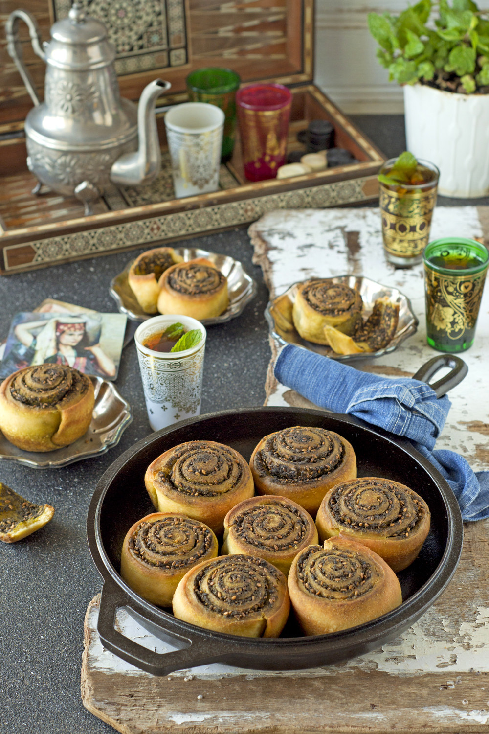 A round pan of tightly rolled buns, covered in a grainy spice mixture with various tea products in the background