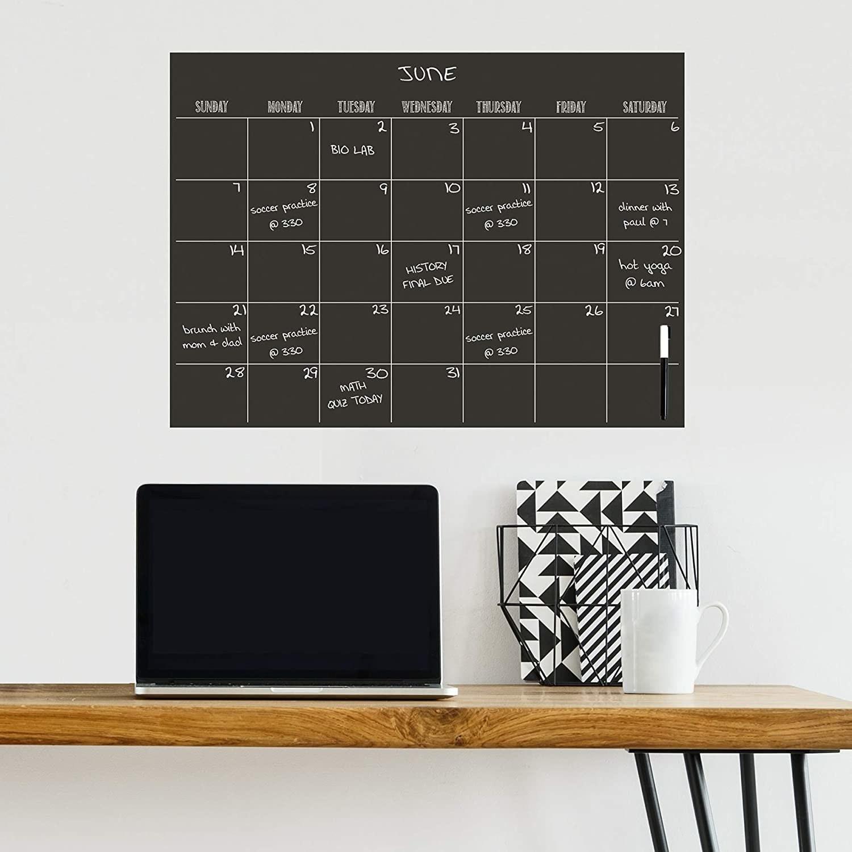 A dry-erase calendar on a wall above a desk
