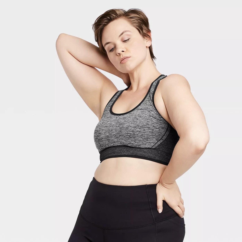 Model is wearing a grey racerback sports bra with black leggings