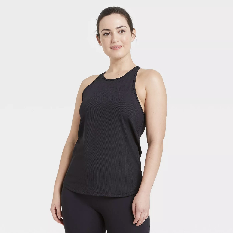Model is wearing a black ribbed tank top and black leggings