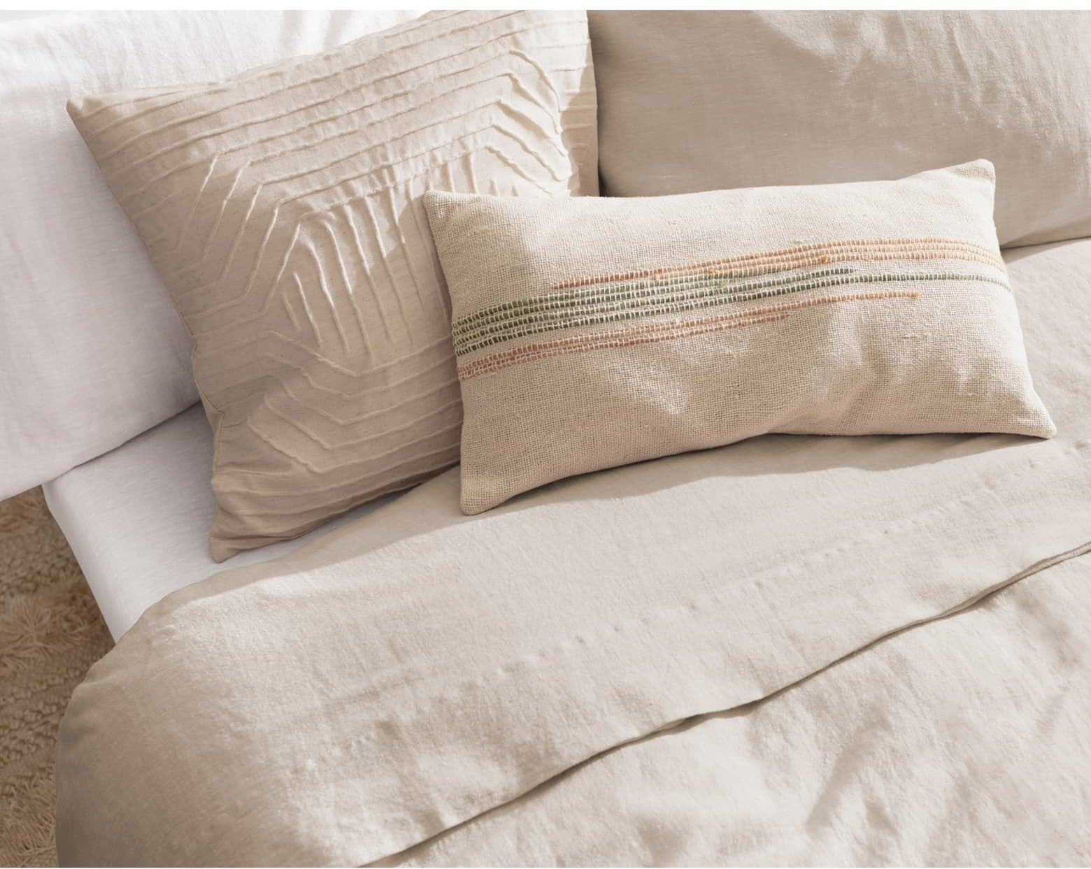 The duvet color in tan on a bed with pillows on it
