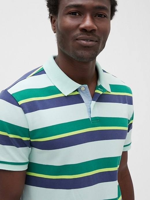 Model wearing a blue, green, and yellow striped polo shirt