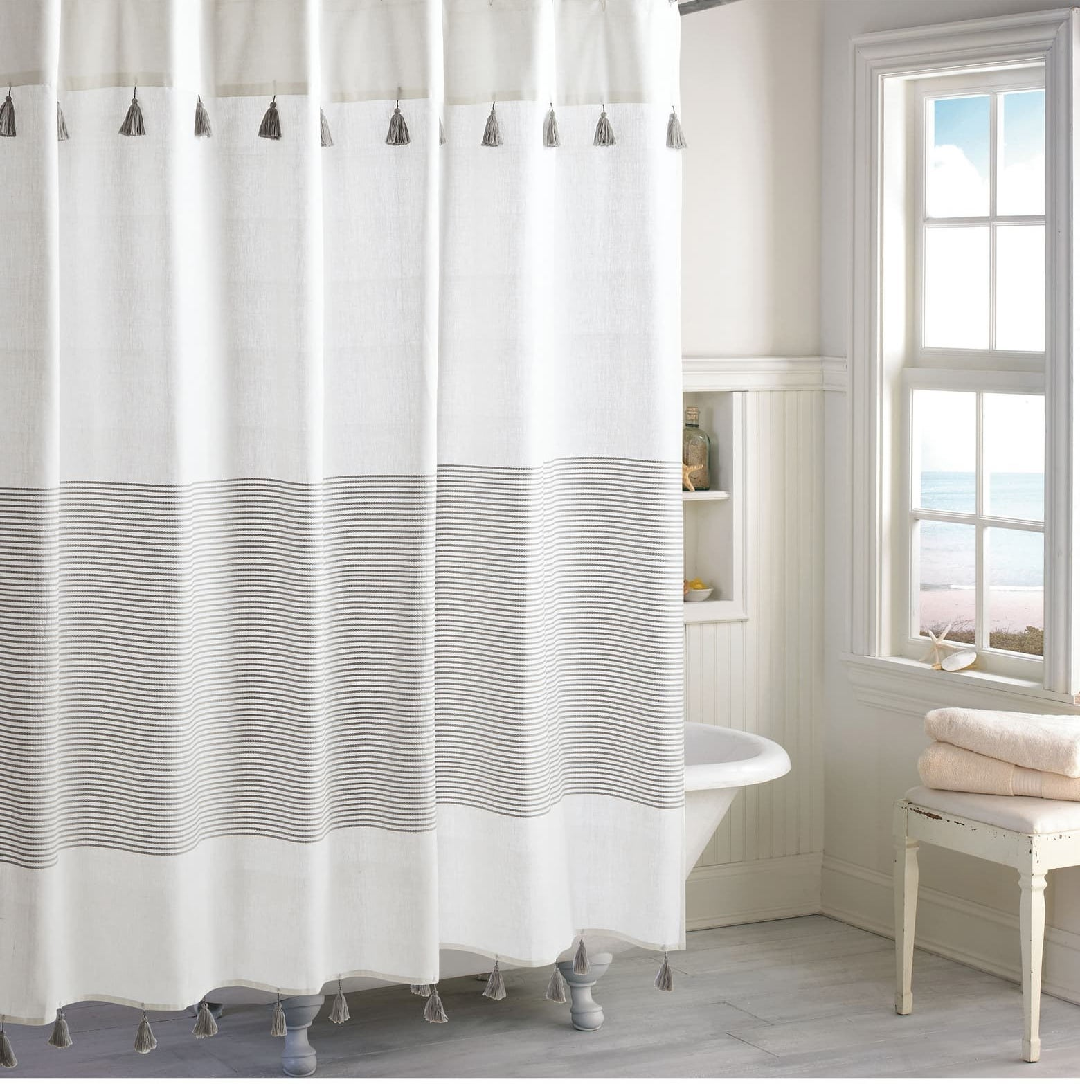 White shower curtain with small stripes in the middle and grey tassels on the top and the bottom