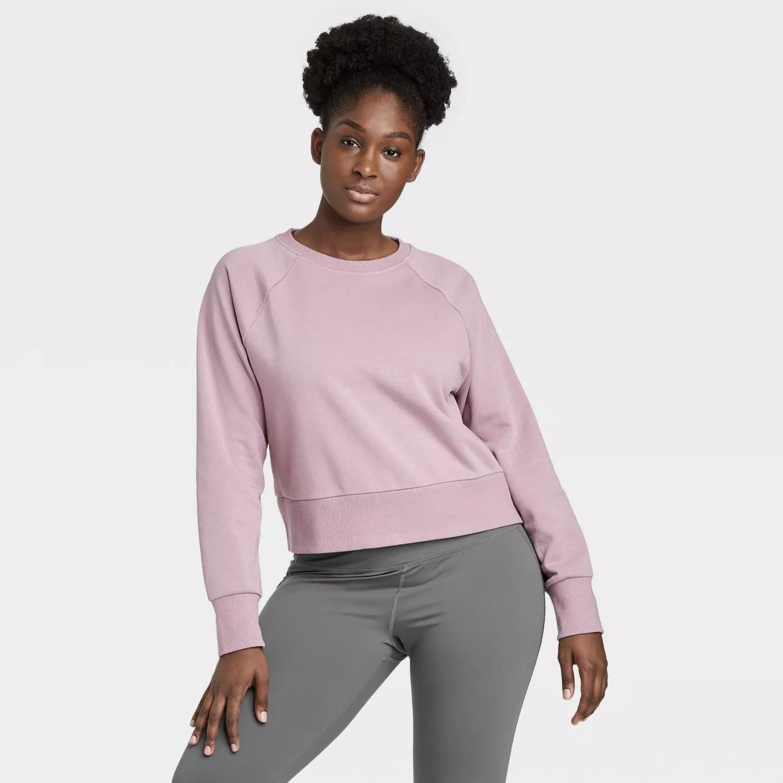 Model is wearing a pale purple sweatshirt with grey leggings