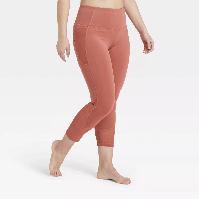 Model is wearing rust capri leggings
