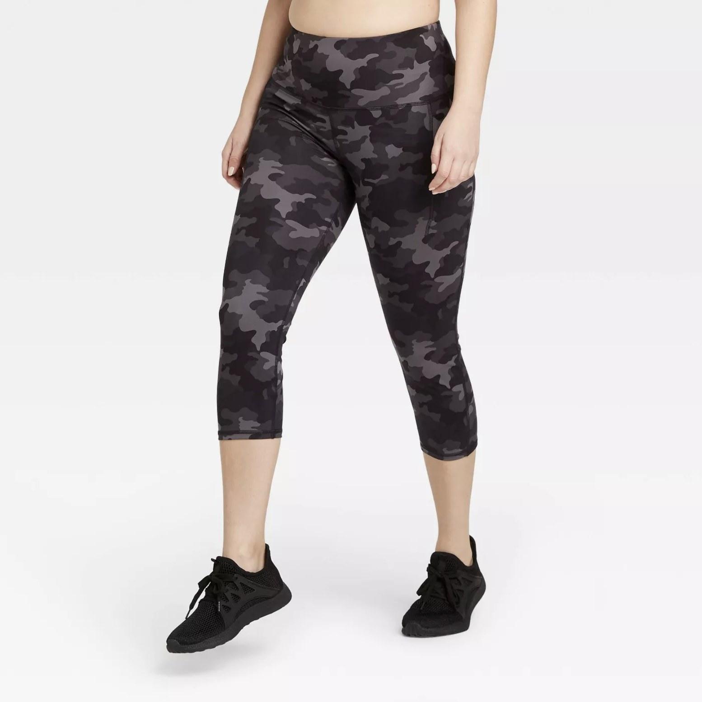 Model is wearing black camo capri leggings with black sneakers