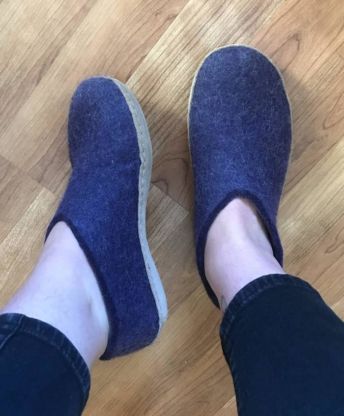 writer in dark purple shoe-like slippers with tan leather soles