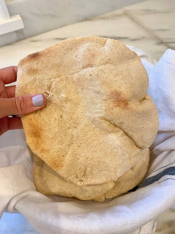 My hand holding a piece of freshly baked pita bread.
