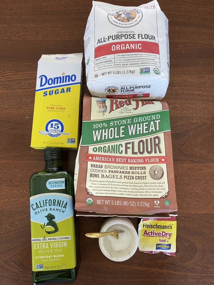 Ingredients for pita -- flours, olive oil, yeast, salt, and sugar -- on a countertop.