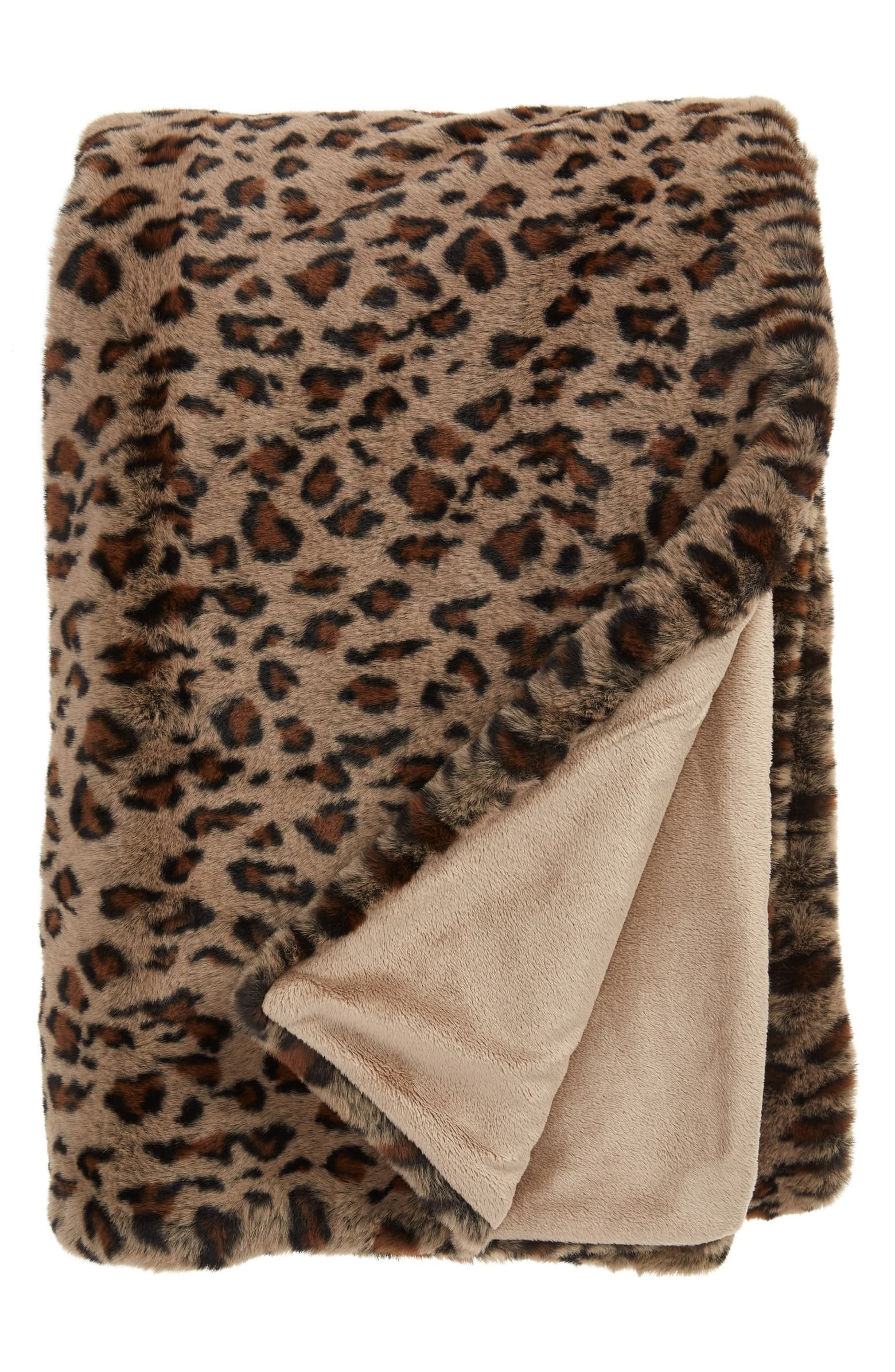 The plush throw blanket with a brown leopard print all over one side and the corner flipped to show the lighter color brown inside
