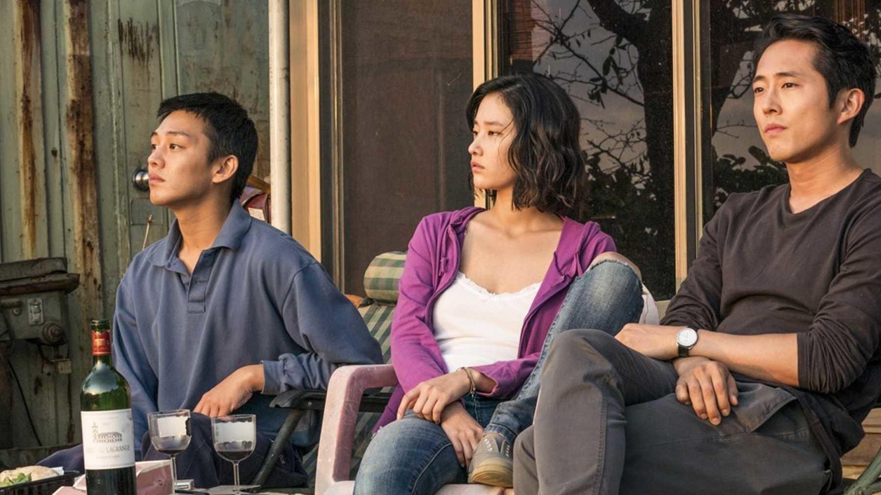 Dos hombres y una mujer sentados mirando el sol tomando vino