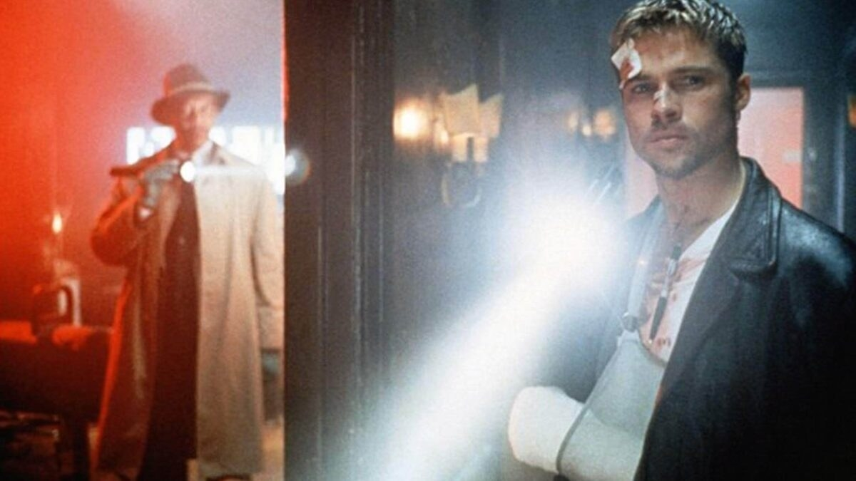 Brad Pitt en película Seven con sangre en la cara y heridas y brazo roto y Morgan Freeman sosteniendo una lámpara con gabardina y sombrero