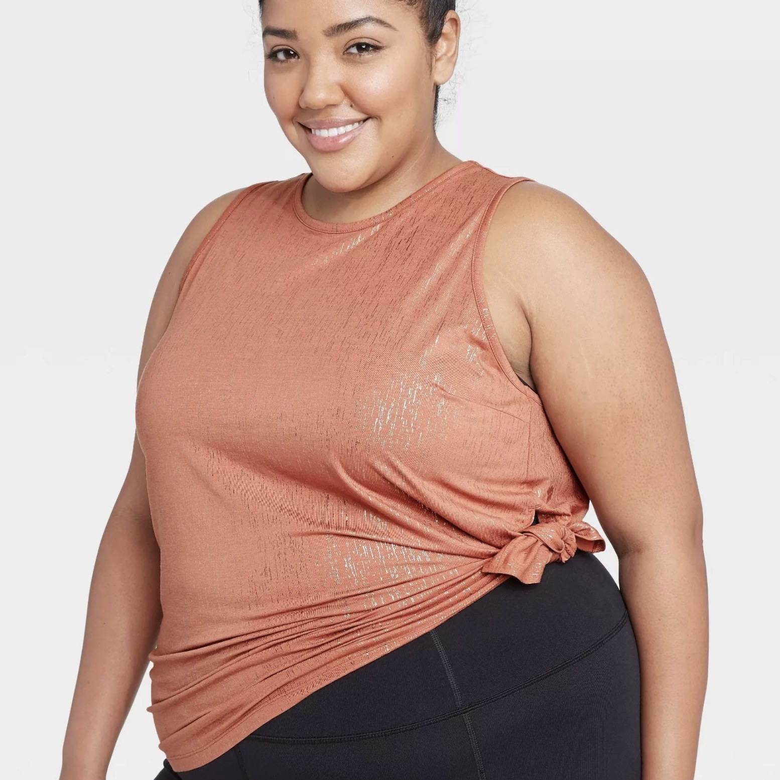 Model is wearing an orange textured tank with a side-tie detail