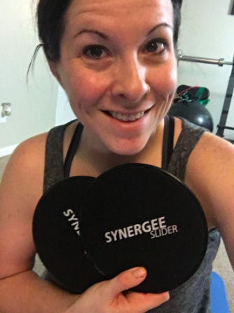 Reviewer holds two black core sliders in their hands after completing a workout