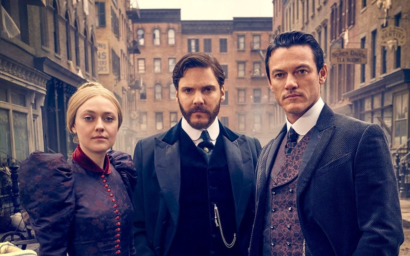 Mujer y dos hombres con ropa de época en medio de la calle