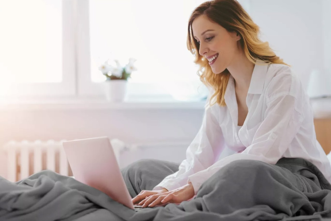 Woman uses blanket while working on laptop