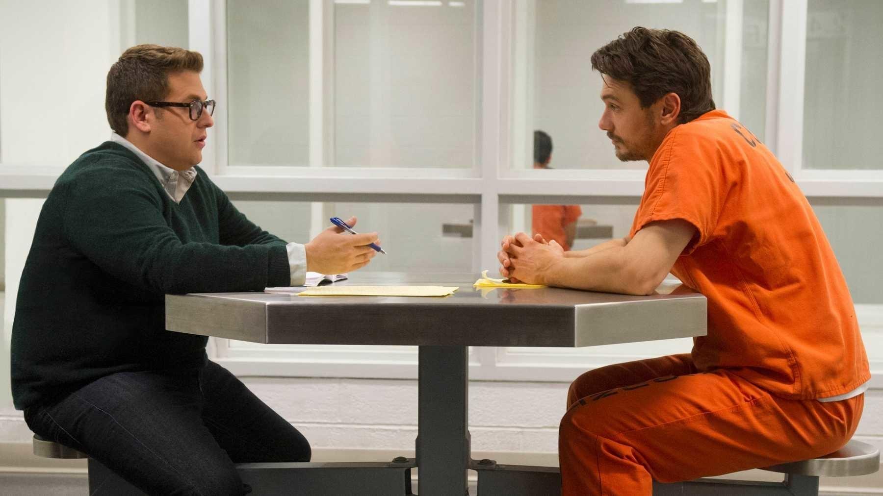 Jonah Hill sentado con James Franco con uniforme de carcelario en película Falsa identidad