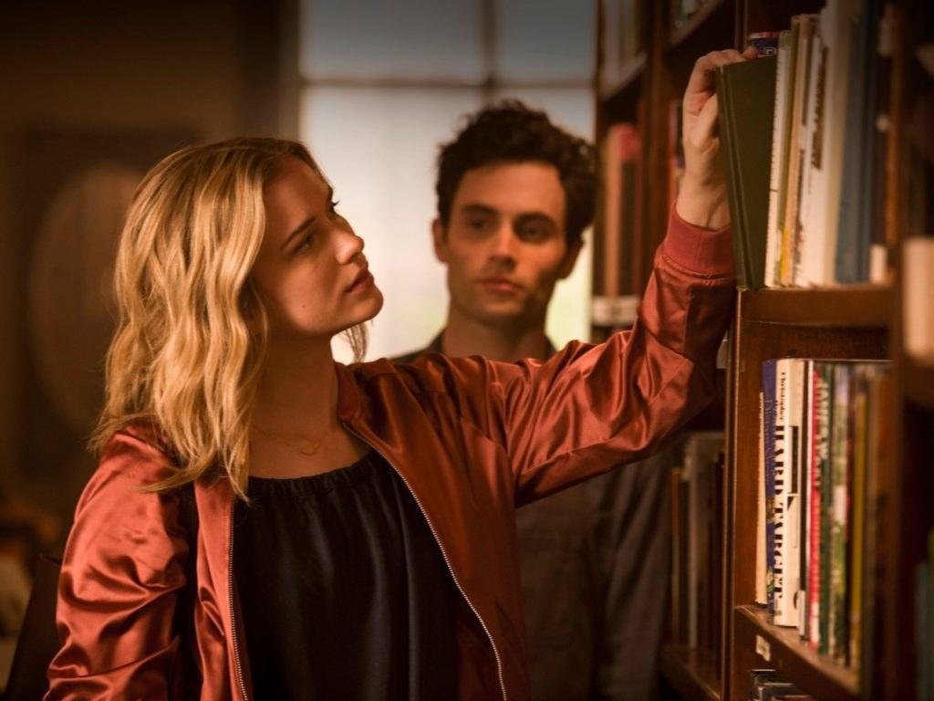 Mujer viendo libros en librería y hombre mirándola