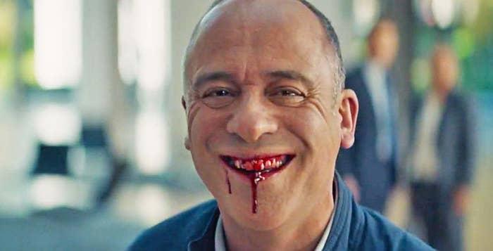 Hombre sonriendo con sangre en los dientes