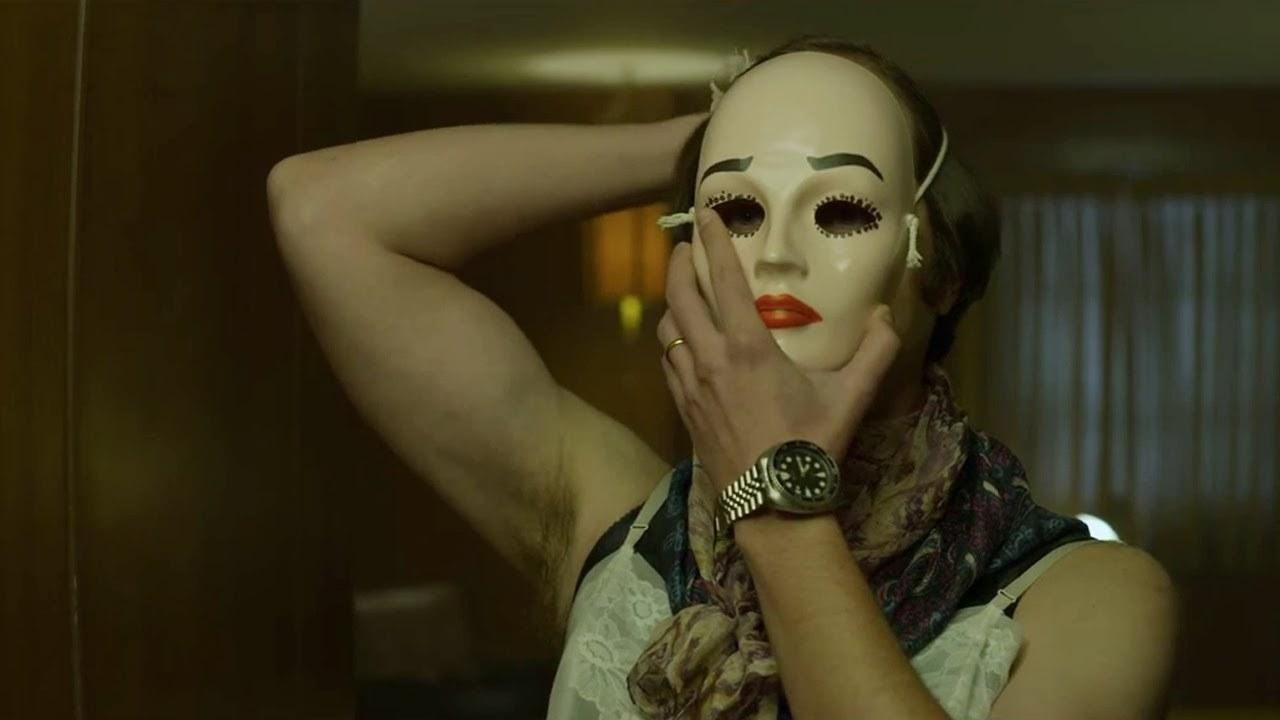 Hombre con máscara perturbadora de mujer y ropa de mujer