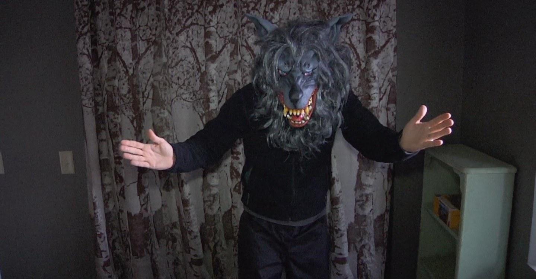 Hombre con máscara de lobo y ropa negra con los brazos abiertos