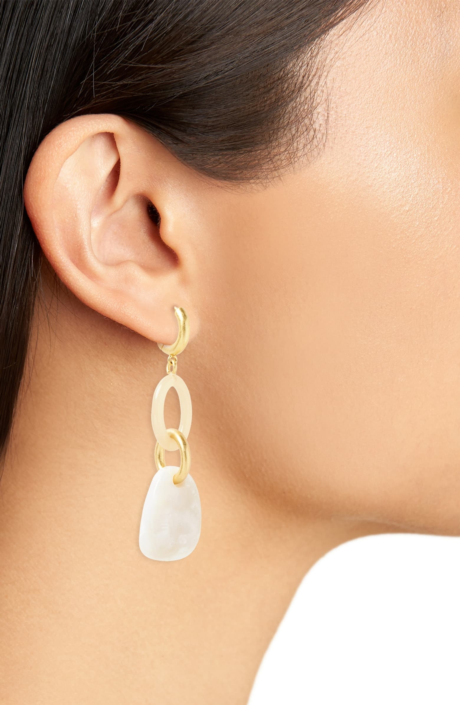 a model wearing the earrings with a gold hoop that connects to a pale pink hoop, connected to another small gold hoop, connected to a white stone
