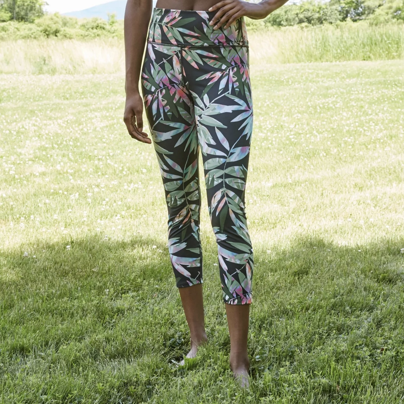 Model is wearing black leggings with a bold tropical print pattern