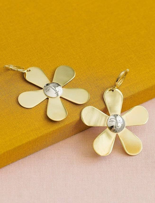 The drop earrings with gold petals and silver centers with a face etched into them
