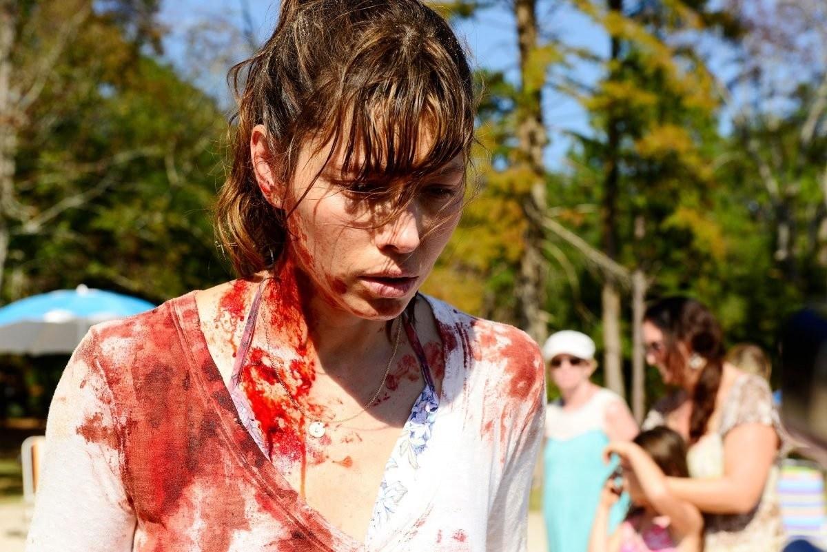 Mujer en la playa con la ropa, cara y pelo llenos de sangre