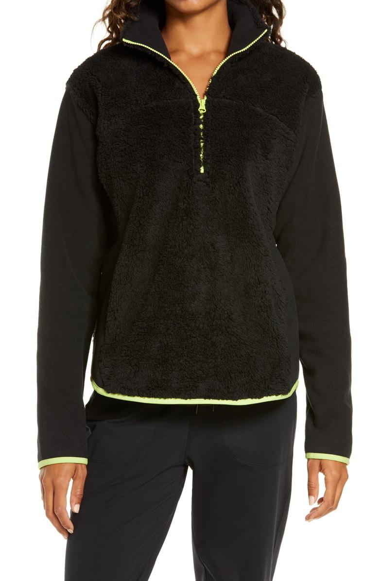 Model wearing Zella Glacier Furry Fleece quarter-zip jacket in black with green detail