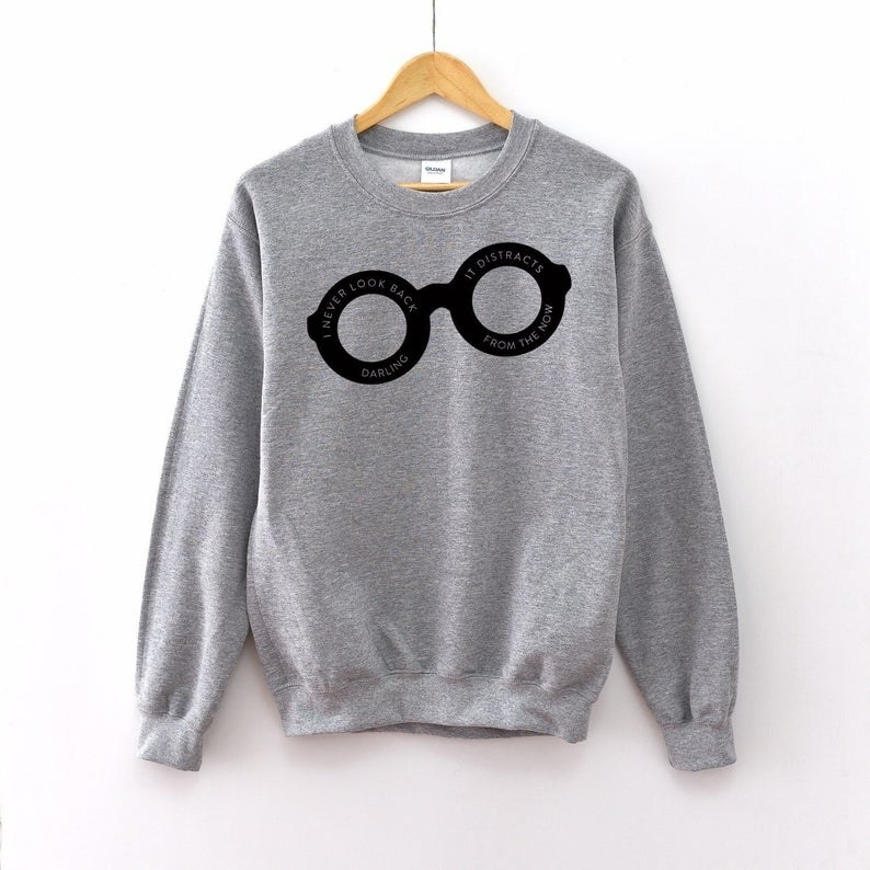 The gray sweatshirt featuring Edna's black glasses printed with a quote