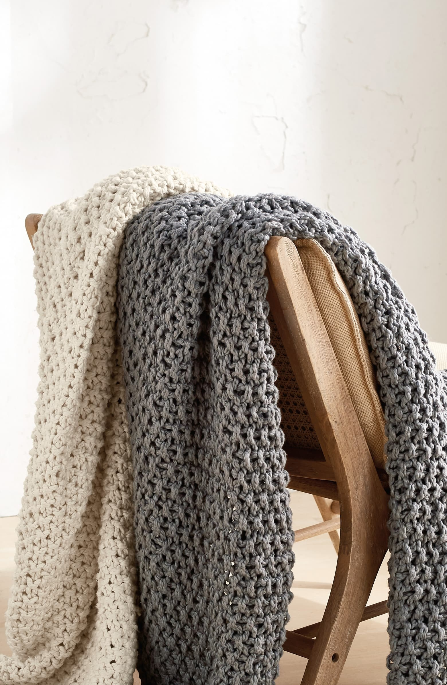 tan and grey knit blankets hanging over a chair