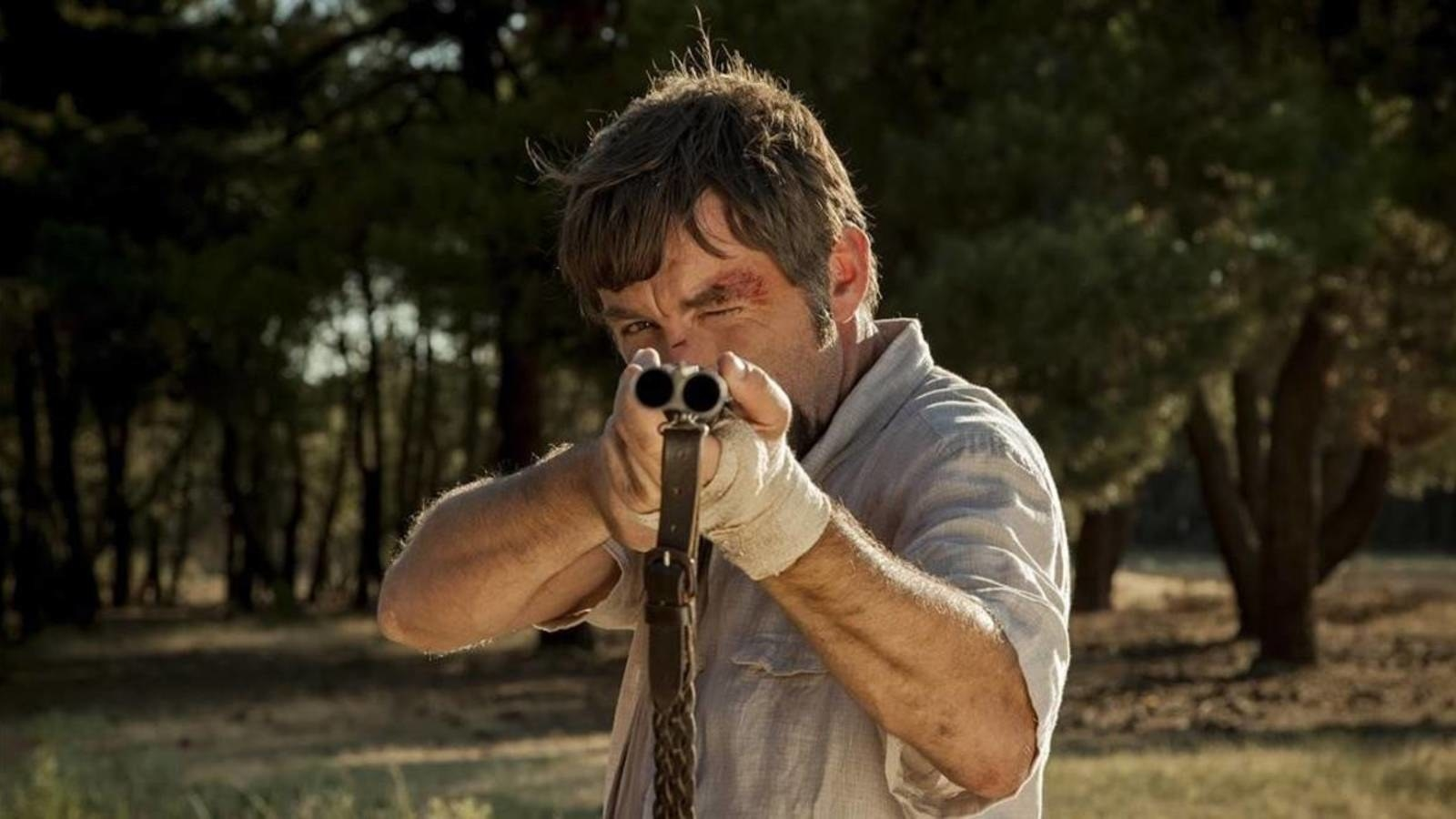 Hombre con sangre en la cara apuntando con escopeta