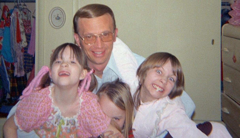 Hombre mayor abrazando a tres niñas en una habitación
