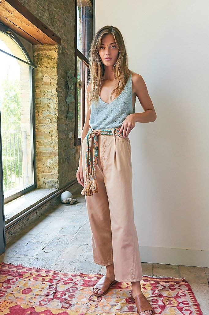 Model wearing the v-neck sweater tank in light blue  with trousers and sandals