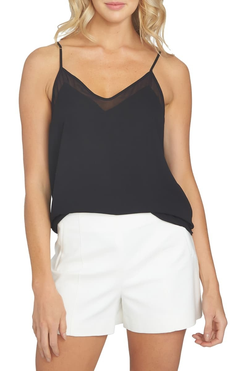 A model wears the 1.STATE chiffon inset cami with white shorts