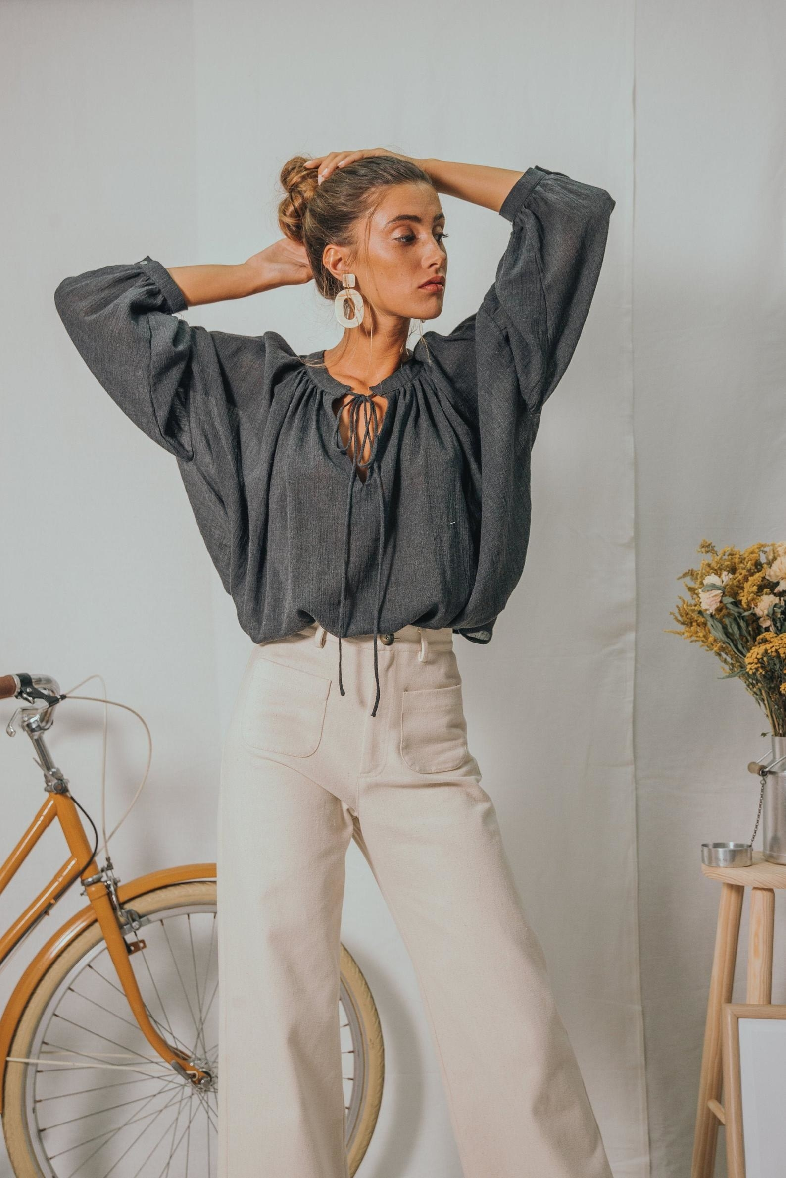 Model wearing the blouse with oversized puff long-sleeves, v-neck and tie in the middle tucked into wide-leg white pants