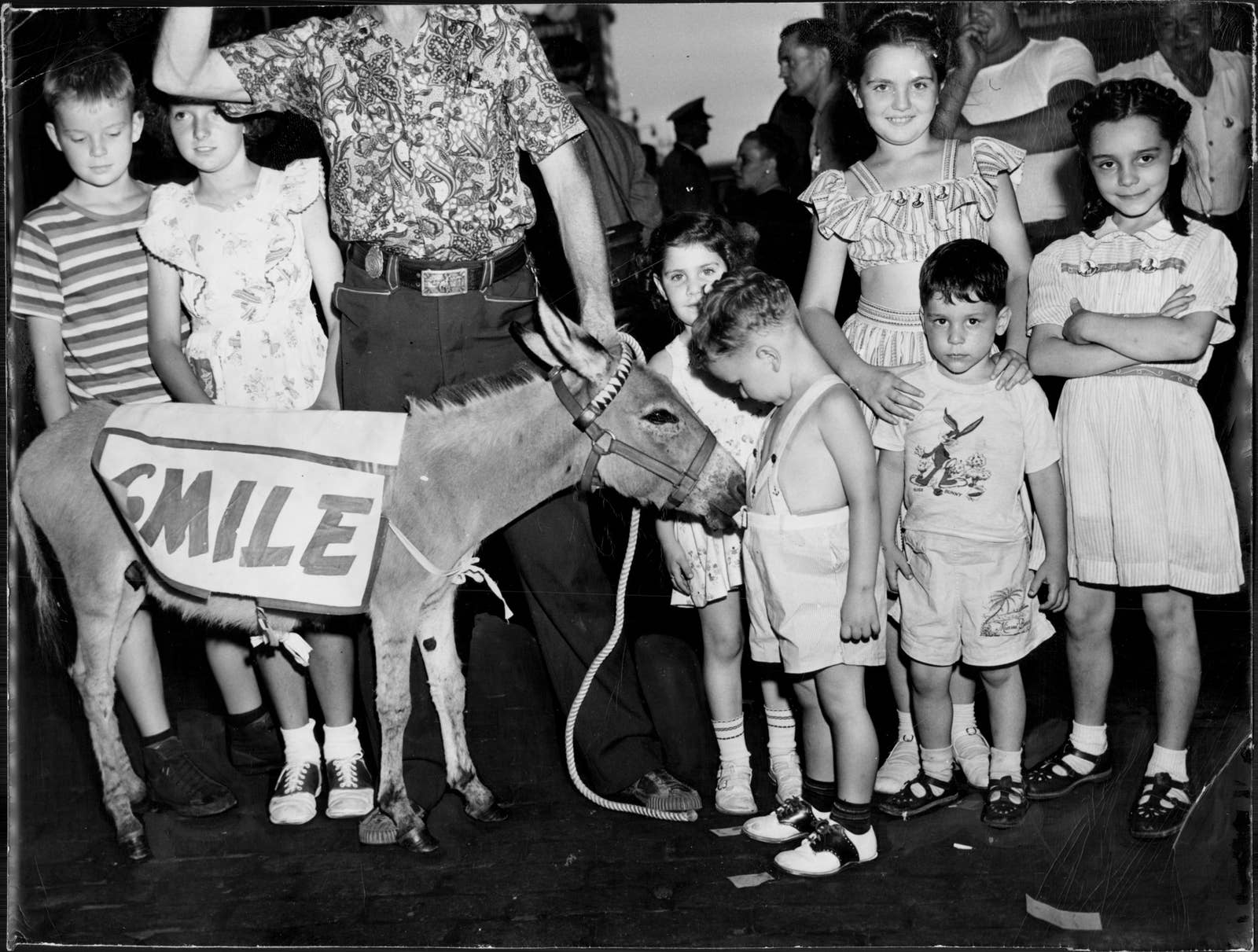 A donkey with a sign that says smile next to a group of kids, most of whom are not smiling
