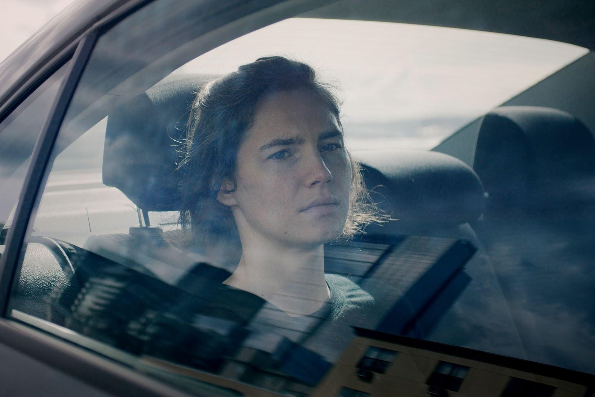 Una mujer mirando a través de la ventana de un auto en el asiento trasero