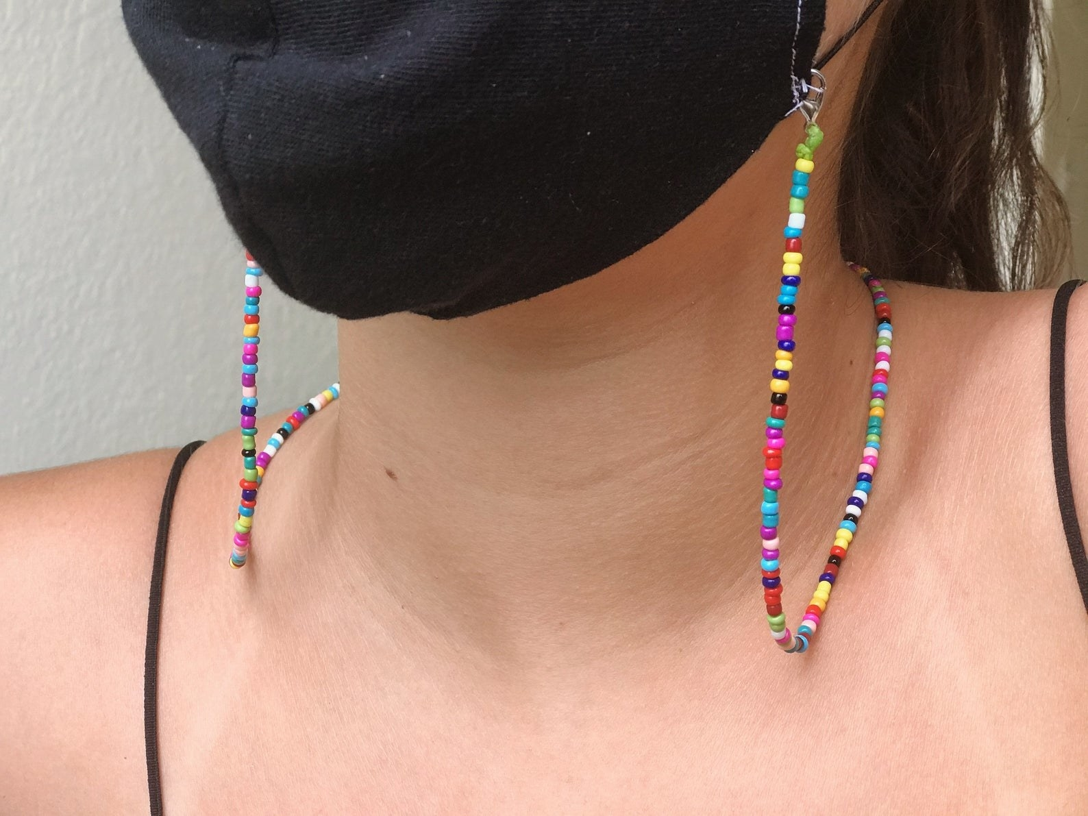 Model wearing a face mask with rainbow beaded chain attached to it