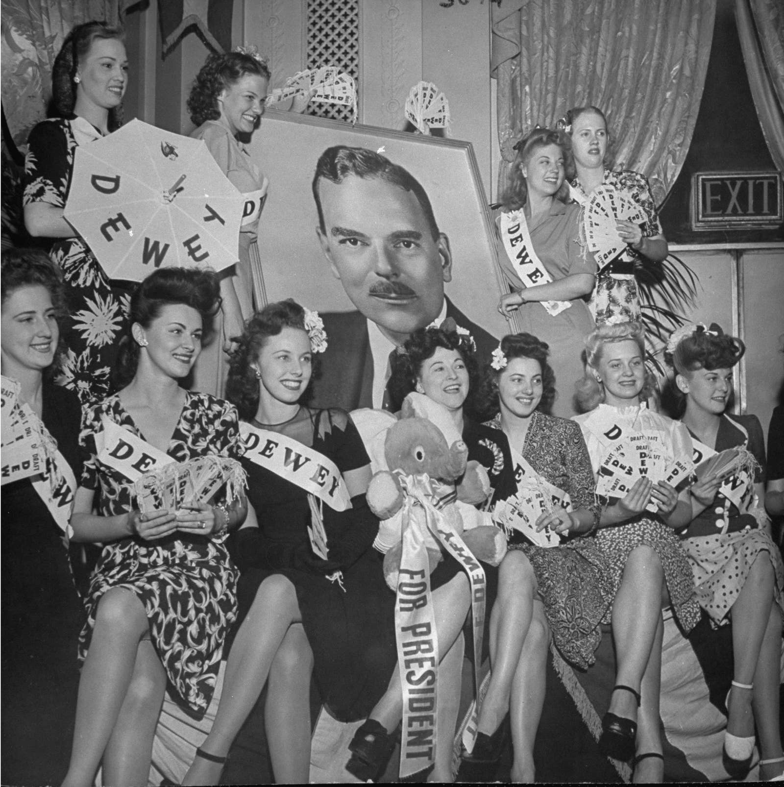 A group of women with ribbons reading dewey sit around a photo of presidential candidate Thomas Dewey