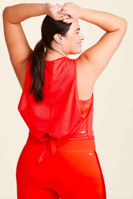 Model wears bright red mesh tank with a tie-back design and matching red leggings