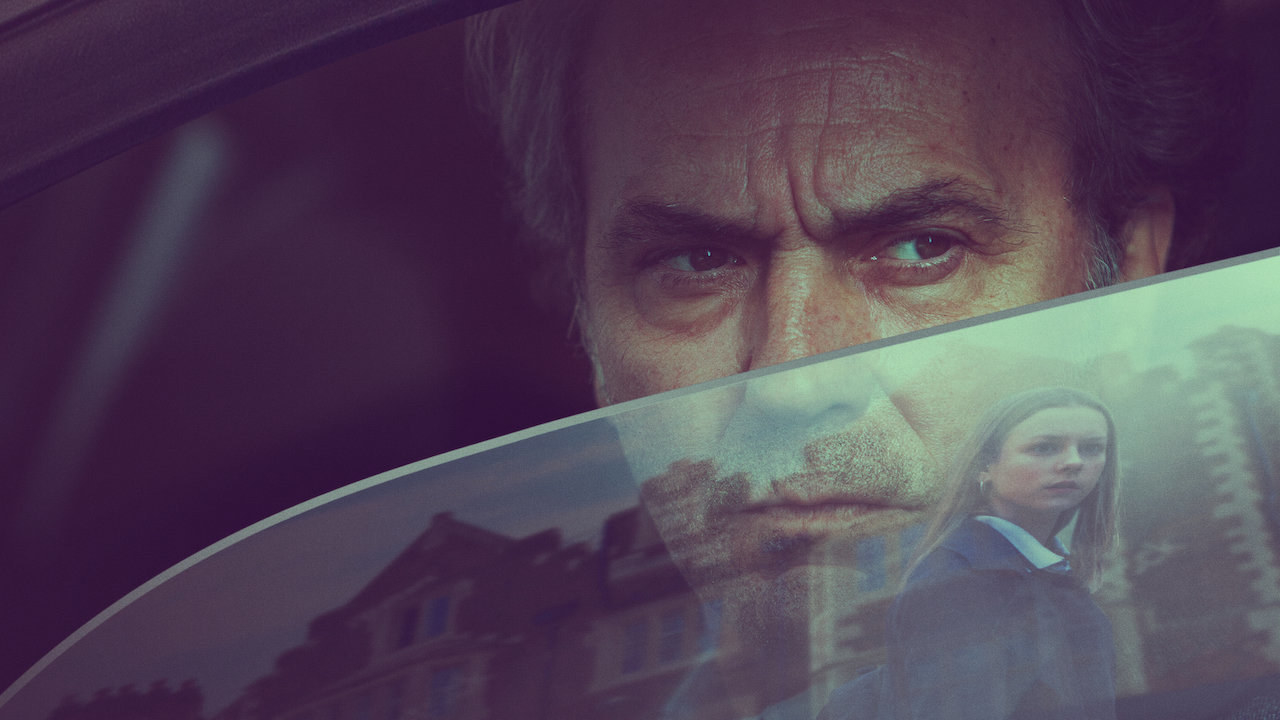Hombre en auto vigilando un vecindario a través de su cristal