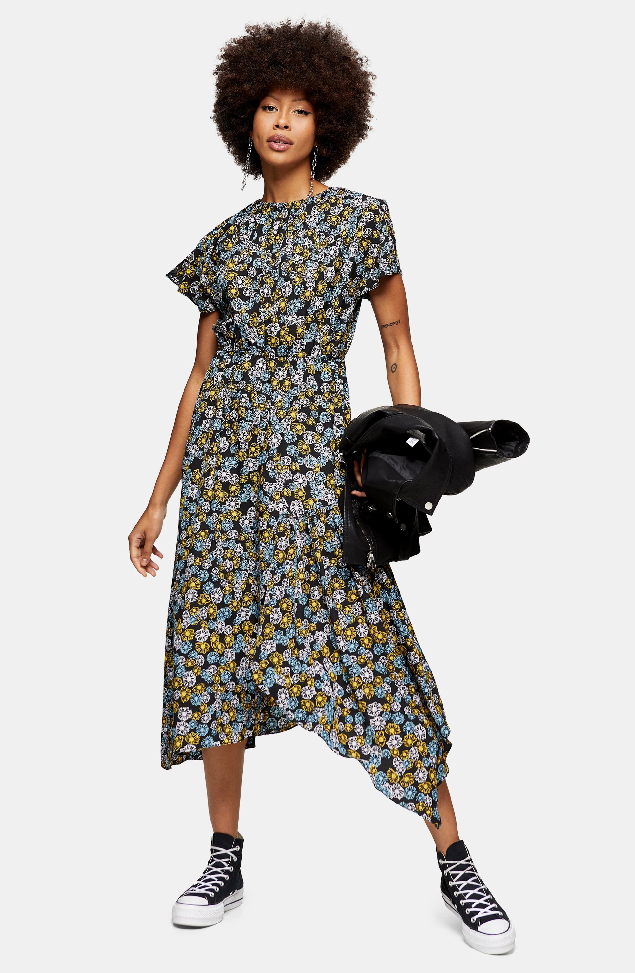 A model wears the Topshop floral print ruched dress with black chucks