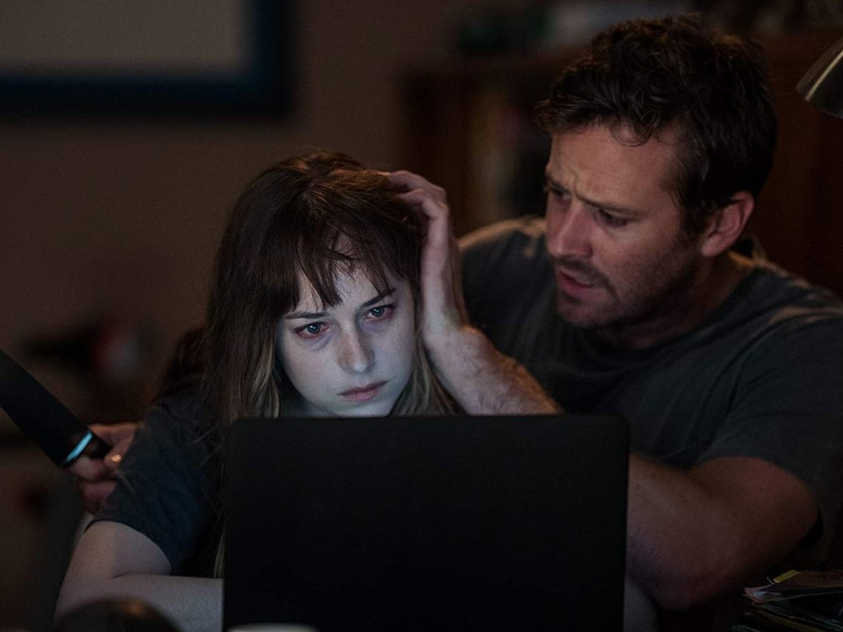 Hombre preocupado acariciando a una mujer pálida mirando la computadora
