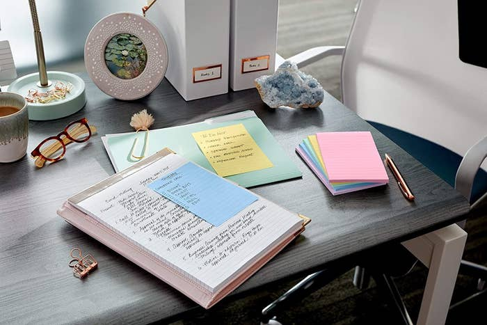 Six pads of eco-friendly Post-it notes next to documents with the sticky notes on them
