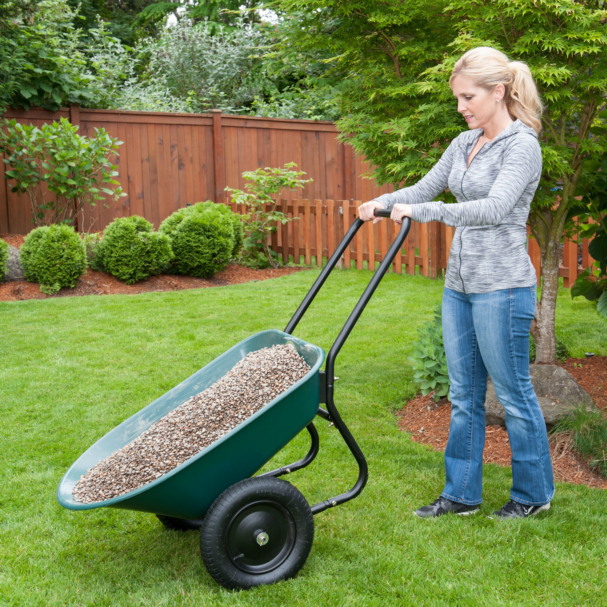 Model using a green wheelbarrow with black wheels and handle