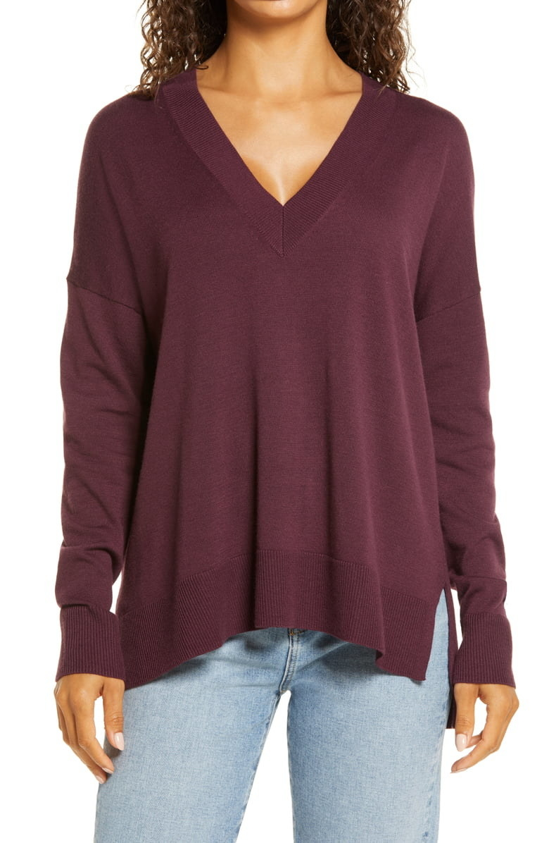 Closeup of a model wearing the Chelsea28 Oversize V-Neck High/Low Sweater in burgundy stem